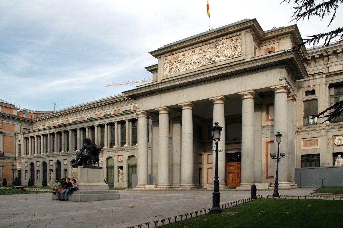 Exterior del Museo del Prado de Madrid decorado con columnas, con una estatua en el frente