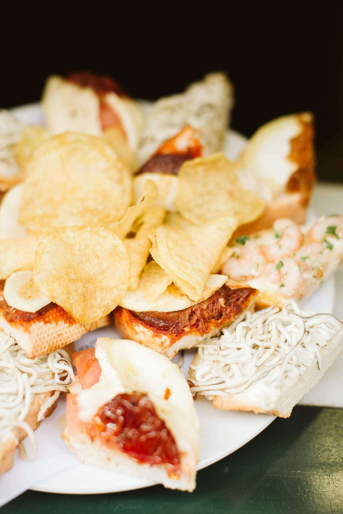 Plato de bocadillos pequeños abiertos con varios aderezos, con un montón de patatas fritas en el medio.