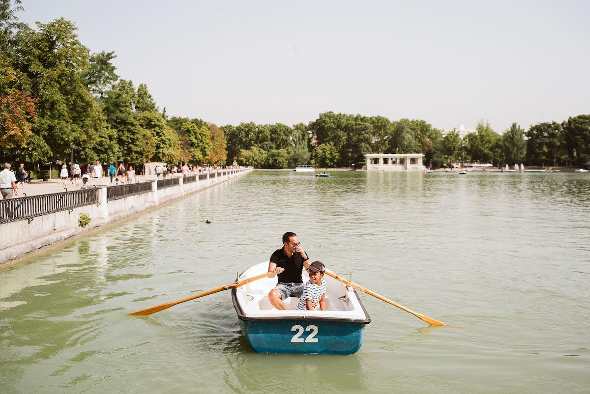 Un padre con su hijo pequeño remando en un bote alrededor de un pequeño lago.