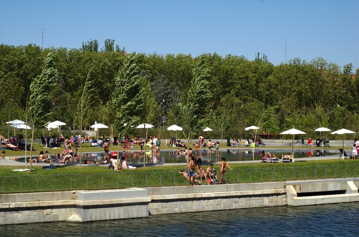 Zona de playa junto al río llena de gente en traje de baño relajándose bajo las sombrillas.