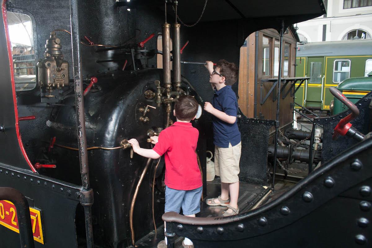 Dos muchachos explorando un viejo vagón de tren negro