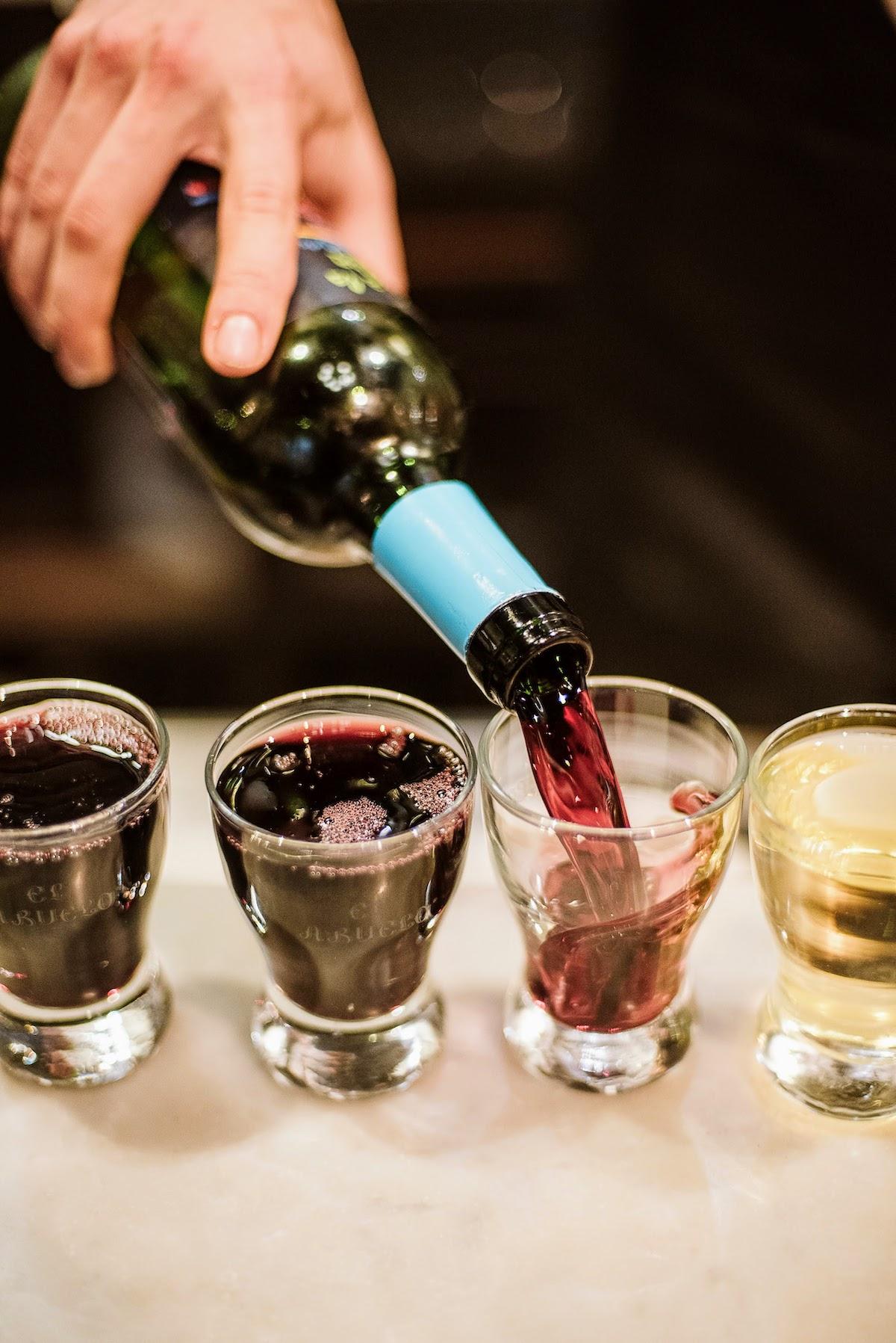 El vino tinto se vierte de una botella en pequeños vasos de chato