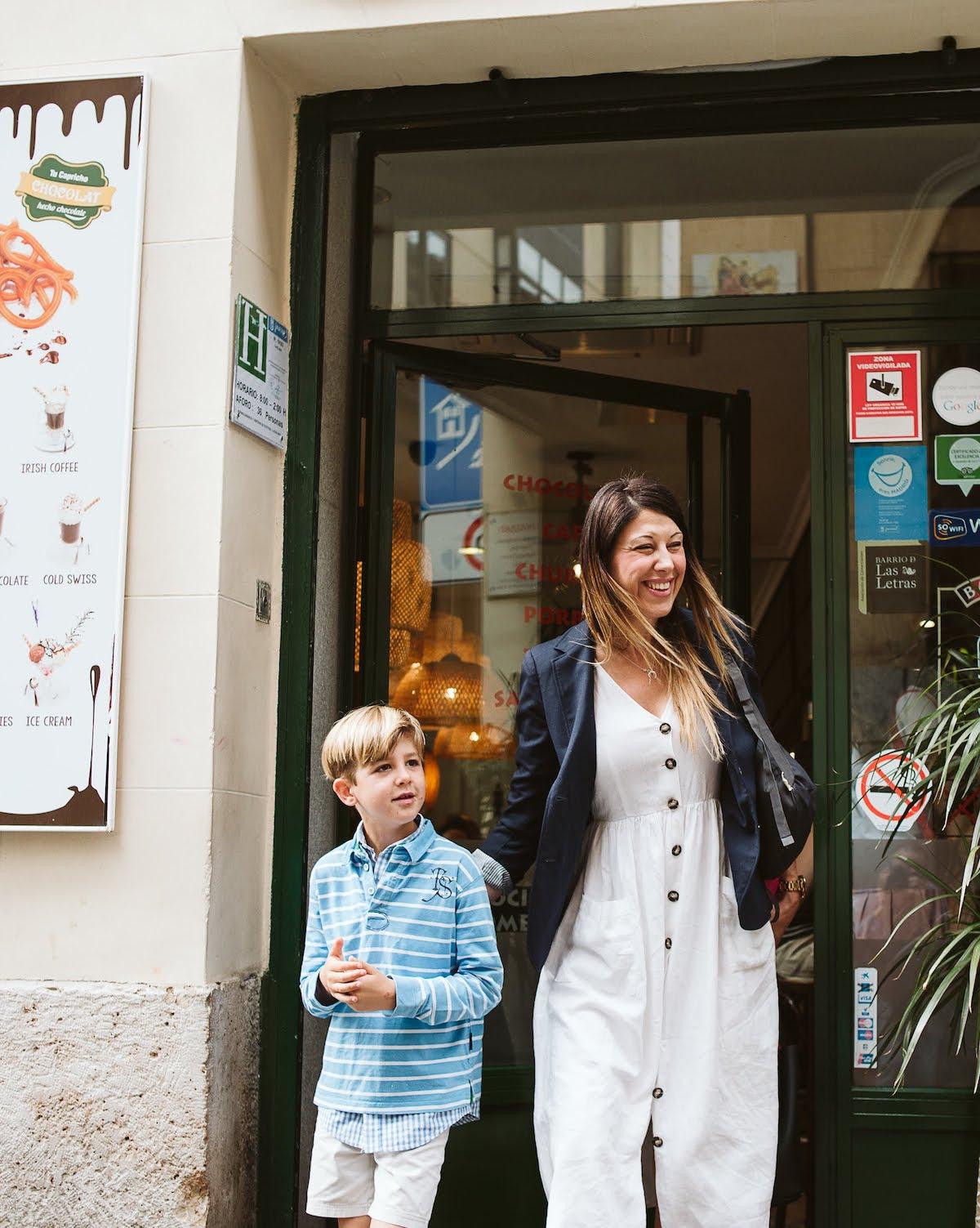 Una mujer y un niño sonriendo saliendo de un café