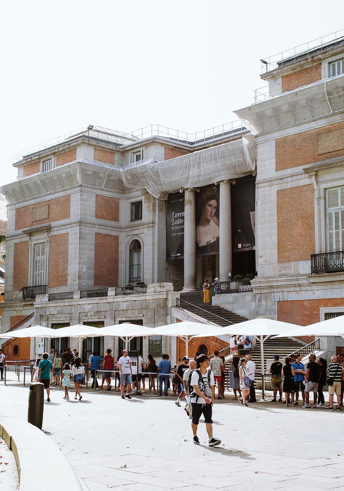 Exterior de un gran edificio de ladrillo y piedra con gente haciendo cola bajo sombrillas en el exterior.