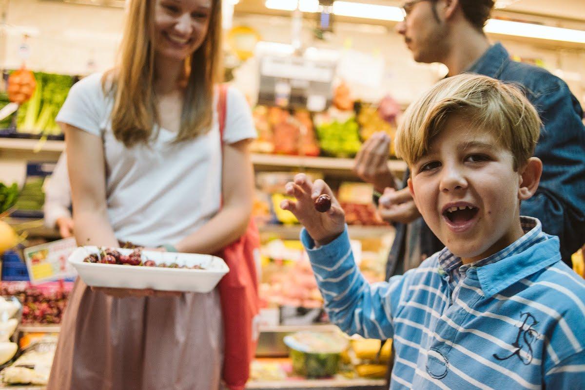 Un joven sonriendo mientras come cerezas en una bandeja blanca frente a un puesto en el mercado