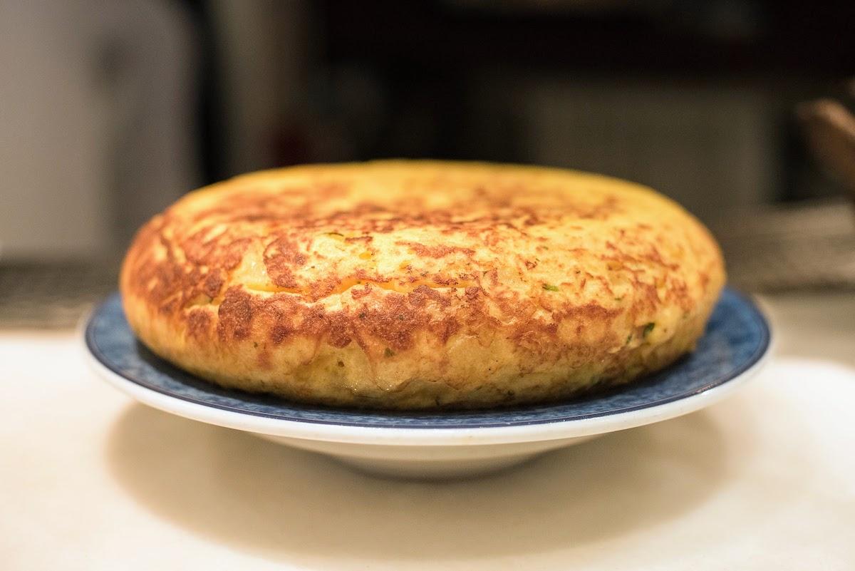Toda una tortilla española en un plato azul y blanco.