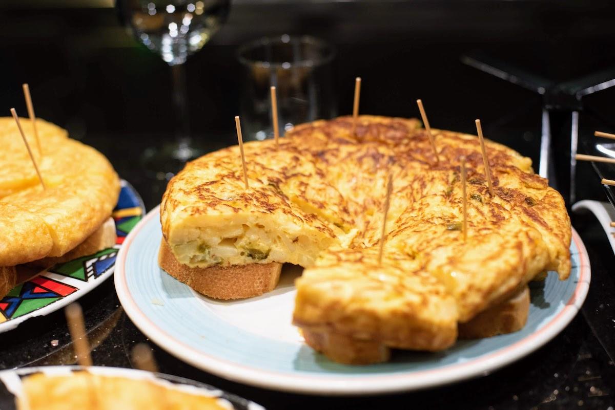 Rebanadas de tortilla de patata y pimiento servidas en trozos pequeños de pan