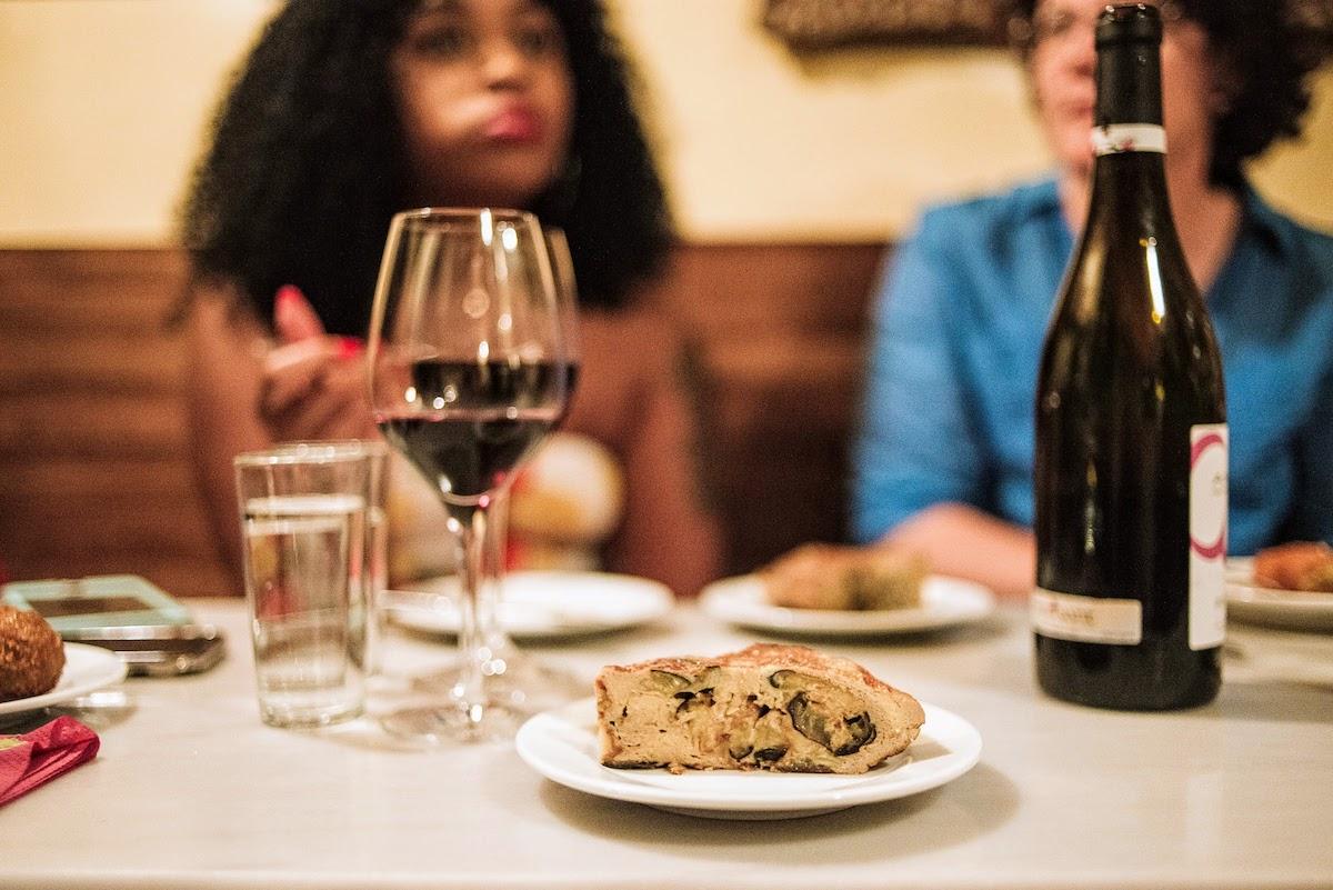 Tortilla de patatas y berenjenas en una mesa junto a una copa de vino tinto