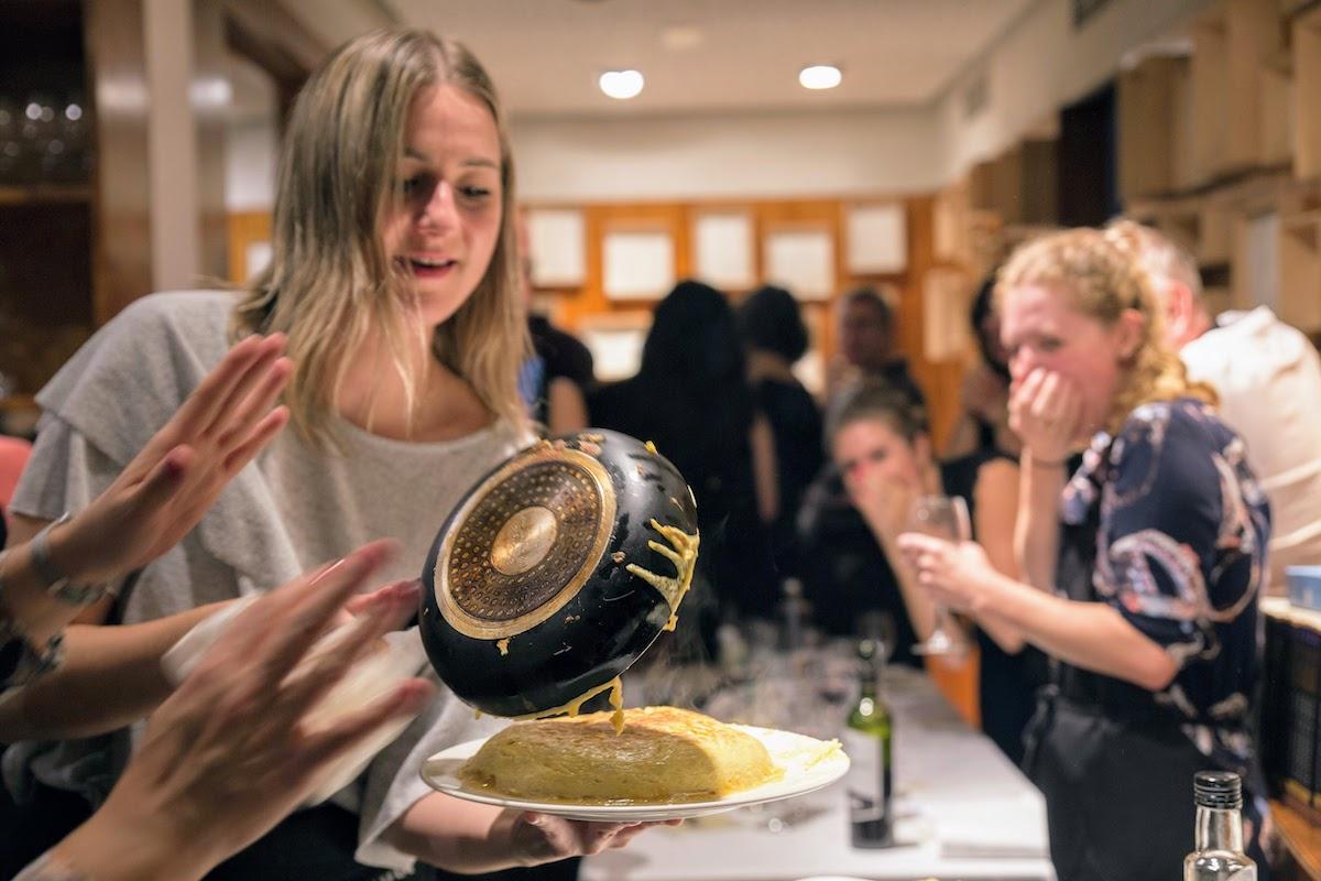 Una mujer derramando una tortilla española de una sartén en un plato mientras varias personas miran